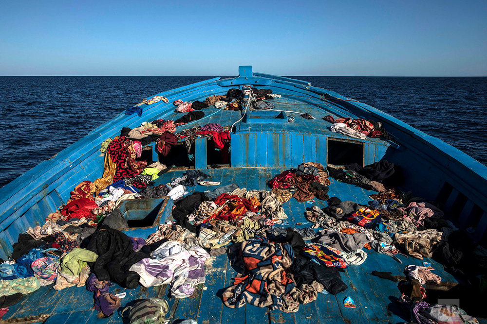 In this Tuesday, Jan. 16, 2018 photo, a wooden boat used by 450 refugees and migrants, mostly from Eritrea, remains abandoned off the Libyan coast after they were rescued by aid workers of the Spanish NGO Proactiva Open Arms, 34 miles north of Kasr-El-Karabulli, Libya. (AP Photo/Santi Palacios)