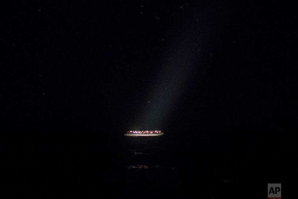 In this Tuesday, Jan. 16, 2018, photo, a rubber boat carrying migrants from different nationalities trying to leave the Libyan coast and reach European soil is spotted by a team of aid workers from the Spanish NGO Proactiva Open Arms, 28 miles north of Al Khums, Libya. (AP Photo/Santi Palacios)