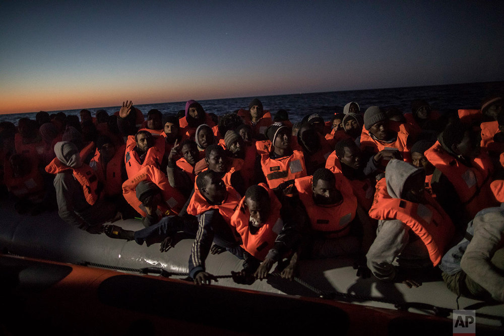 In this Tuesday, Jan. 16, 2018, photo, Sub-Saharan refugees and migrants from different nationalities trying to leave the Libyan coast and reach European soil aboard an overcrowded rubber boat are rescued by a team of aid workers from the Spanish NGO Proactiva Open Arms, 28 miles north of Al Khums, Libya. (AP Photo/Santi Palacios)