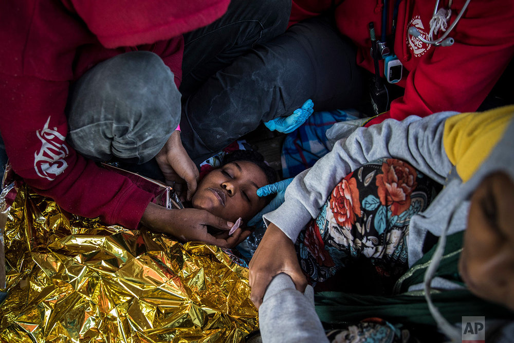 In this Thursday, Jan. 18, 2018 photo a doctor from the Spanish NGO Proactiva Open Arms assists an Eritrean woman as the organization's rescue vessel heads to Italy with more than 300 refugees and migrants on board. (AP Photo/Santi Palacios)