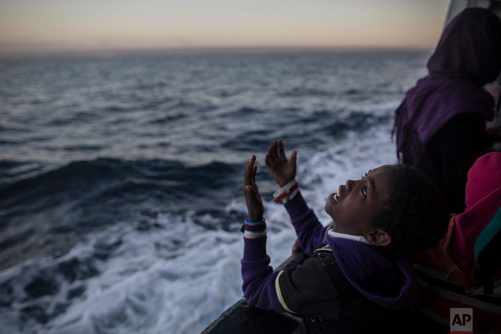 In this Friday, Jan. 19, 2018 photo a child from Eritrea sings to celebrate his arrival to Europe aboard the Spanish NGO Proactiva Open Arms rescue vessel, Pozzallo, Sicily, Italy. (AP Photo/Santi Palacios)