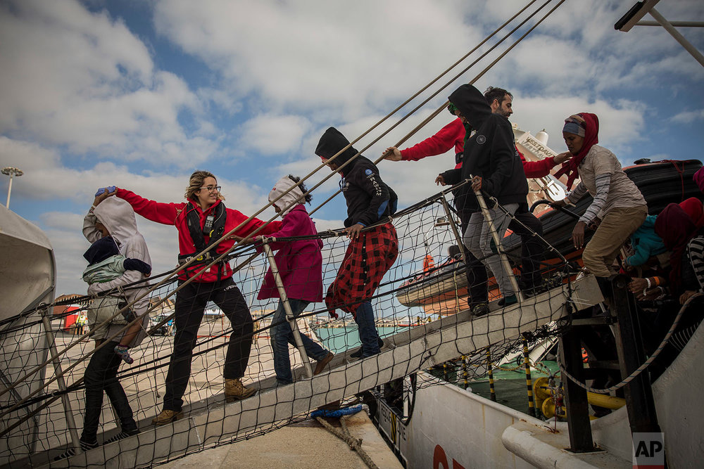 In this Friday, Jan. 19, 2018 photo aid workers from the Spanish NGO Proactiva Open Arms help refugees and migrants to disembark from the rescue vessel, at the port of Pozzallo, in Sicily, Italy. (AP Photo/Santi Palacios)