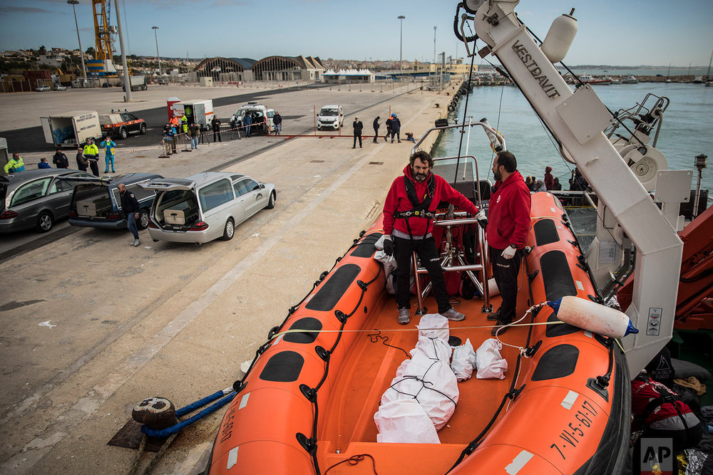 In this Friday, Jan. 19, 2018 photo aid workers from the Spanish NGO Proactiva Open Arms wait to disembark the lifeless bodies of an Eritrean man and 2 babies from the organization's rescue vessel, at the port of Pozzallo, in Sicily, Italy. (AP Photo/Santi Palacios)