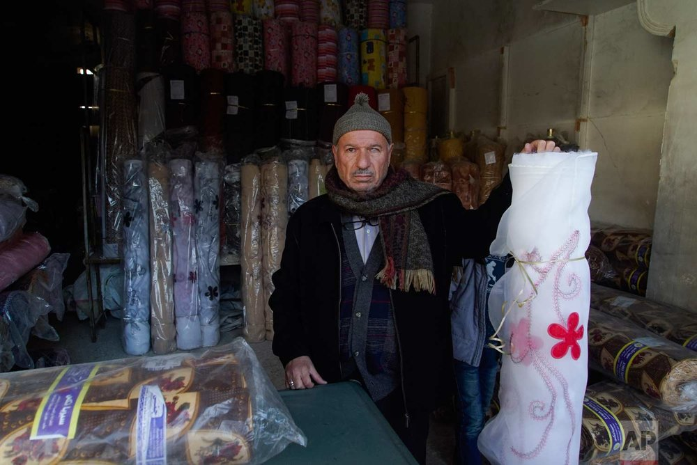 In this picture taken Sunday, Jan. 21, 2018, Mahmoud Mimeh, textile shops owner at the old market, poses for a picture inside his shop in the old city of Aleppo, Syria. (AP Photo/Mstyslav Chernov) |  See these photos on AP Images