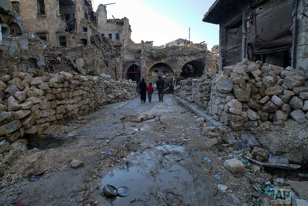 In this picture taken Sunday, Jan. 21, 2018, a Syrian family walks through the destruction of the old market in the old city of Aleppo, Syria. (AP Photo/Mstyslav Chernov) |  See these photos on AP Images