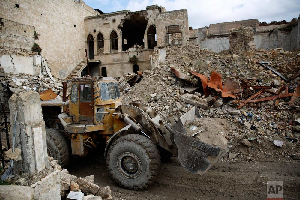 In this picture taken Thursday, Jan. 18, 2018, a bulldozer removes rubble from damage of the old market in the old city of Aleppo, Syria. (AP Photo/Hassan Ammar) |  See these photos on AP Images
