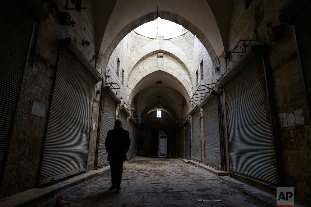 In this picture taken Sunday, Jan. 21, 2018, a Syrian man walks through the old market in the old city of Aleppo, Syria. (AP Photo/Mstyslav Chernov) |  See these photos on AP Images