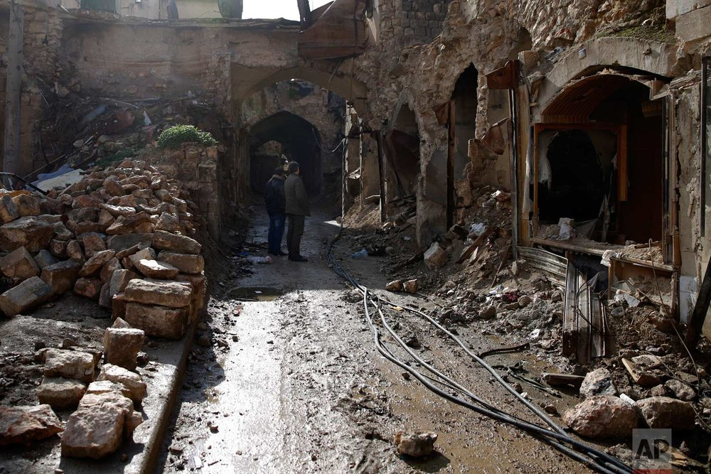 In this picture taken Thursday, Jan. 18, 2018, Syrian men check the destruction of the old market in the old city of Aleppo, Syria. (AP Photo/Hassan Ammar) |  See these photos on AP Images