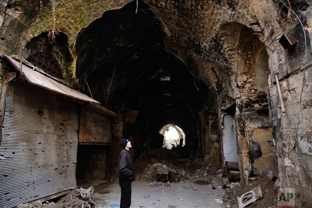 In this Thursday, Jan. 18, 2018 photo, a Syrian man checks the destruction of the old market in the old city of Aleppo, Syria. (AP Photo/Hassan Ammar) |  See these photos on AP Images