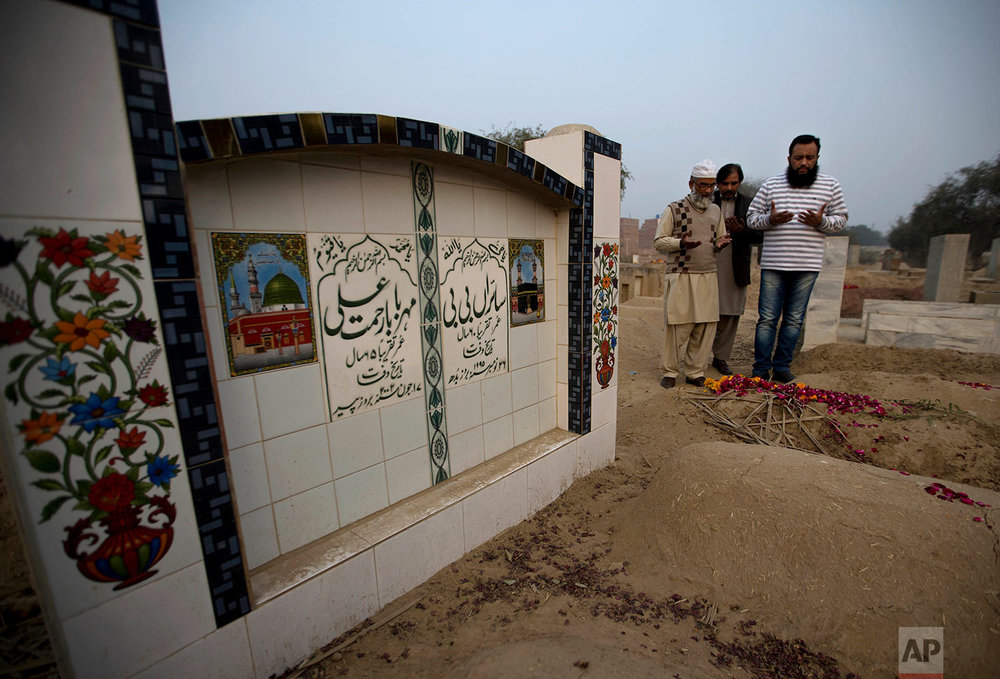 In this Thursday, Jan. 18, 2018 photo Mohammed Amin, left, offer prayers at a grave of his seven year old daughter Zainab Ansari in Kasur, Pakistan. (AP Photo/B.K. Bangash)  |  See these photos on AP Images