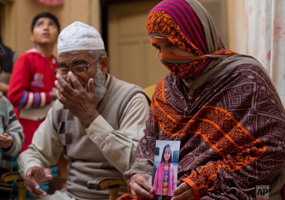 In this Thursday, Jan. 18, 2018 photo, Nusrat holds a photo of her daughter, Zainab Ansari, who was raped and killed, as her husband, Mohammed Amin in Kasur, sits beside her in Kasur, Pakistan. (AP Photo/B.K. Bangash)  |  See these photos on AP Images