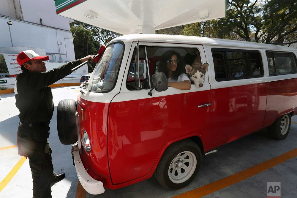 In this Wednesday, Dec. 27, 2017 photo, Jair Benavides has his Volkswagen van fueled at a gas station as he takes his dogs on a day trip, in Mexico City. Jair and his wife Mariam Gutierrez de Velasco take their dozens of dogs out on field trips outside the city so that they can exercise. (AP Photo/Marco Ugarte)