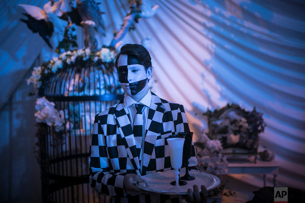 "A waiter is paint as colors of a chess game during the ""Grand Bal Christian Dior"" during the Haute Couture Spring-Summer 2018 fashion collection presented in Paris, Monday, Jan. 22, 2018. (AP Photo/Kamil Zihnioglu)  