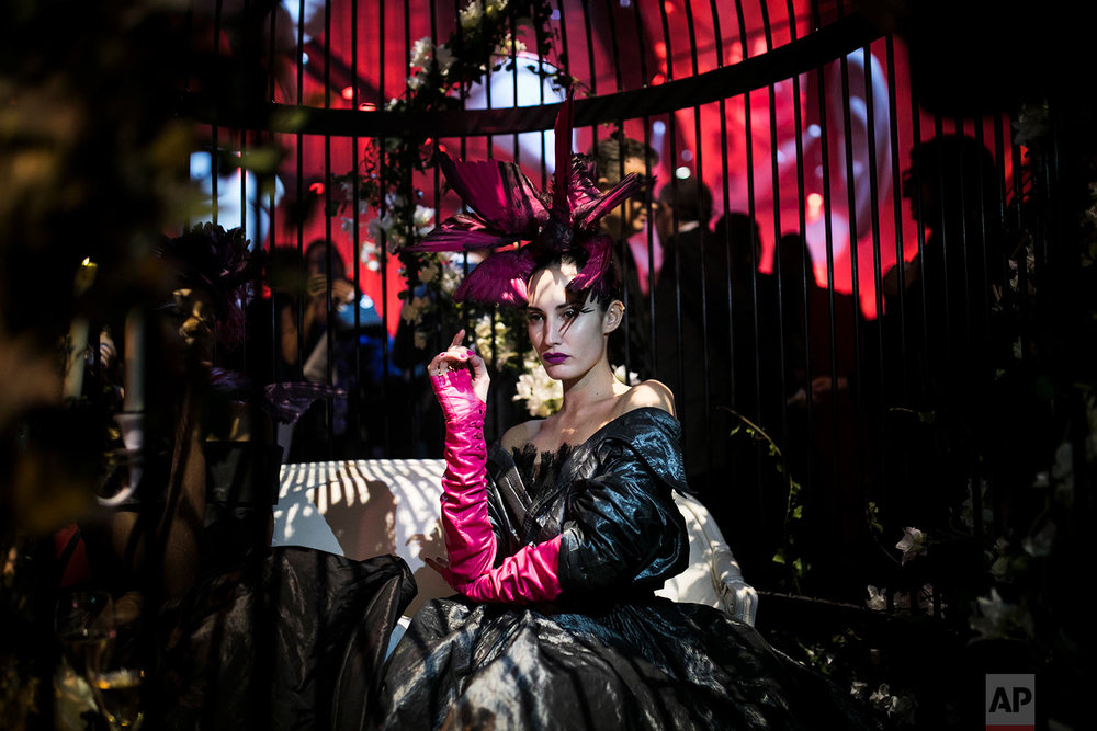 "A performer sits in a huge cage as she attends the ""Grand Bal Christian Dior"" during the Haute Couture Spring-Summer 2018 fashion collection presented in Paris, Monday, Jan. 22, 2018. (AP Photo/Kamil Zihnioglu) 