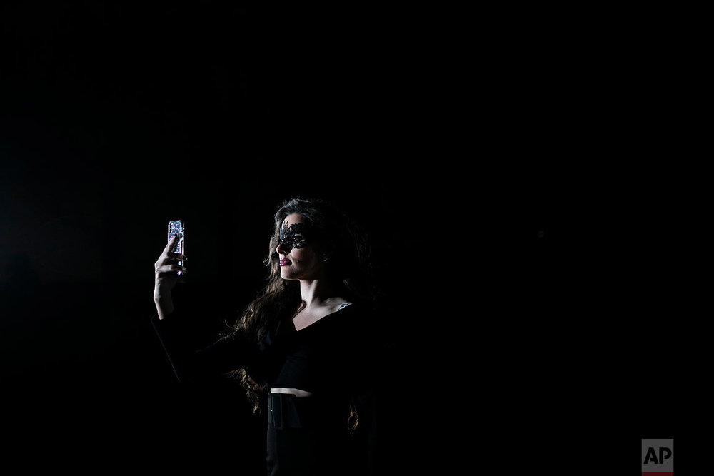 "A masked guest takes a selfie as she attends the ""Grand Bal Christian Dior"" during the Haute Couture Spring-Summer 2018 fashion collection presented in Paris, Monday, Jan. 22, 2018. (AP Photo/Kamil Zihnioglu 