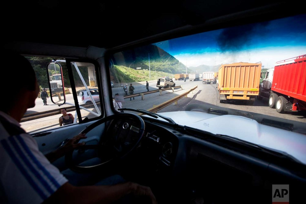 In this Jan. 23, 2018 photo, Carlos Del Pino steers his truck loaded with bulk rice, behind other grain trucks, as he departs the port under the escort of Venezuelan Bolivarian National Guards to protect the grain-carrying convoy from looters as they cross Puerto Cabello Venezuela. (AP Photo/Fernando Llano)  See these photos on AP Images