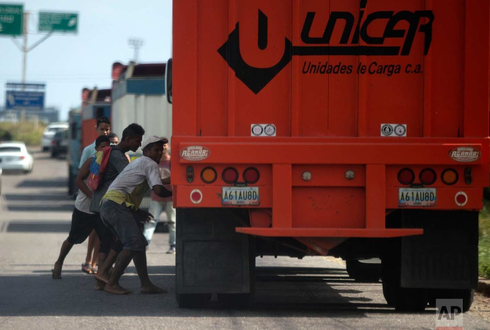 In this Jan. 23, 2018 photo, men try to steal rice from a cargo truck arriving to the port in Puerto Cabello, Venezuela. (AP Photo/Fernando Llano)  See these photos on AP Images