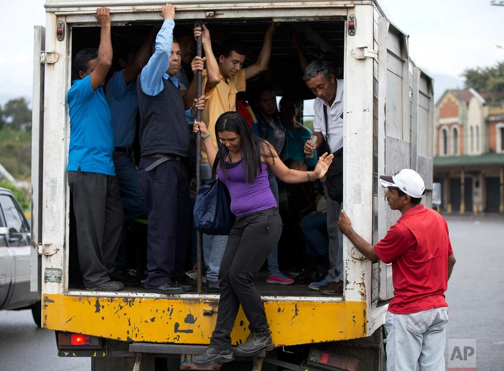 In this Jan. 22, 2018 photo, a woman gets off a cargo truck serving as public transportation in Villa de Cura, Venezuela. Some truck owners prefer to carry passengers instead of merchandise because of looting that targets grain-carrying cargo. (AP Photo/Fernando Llano)  See these photos on AP Images