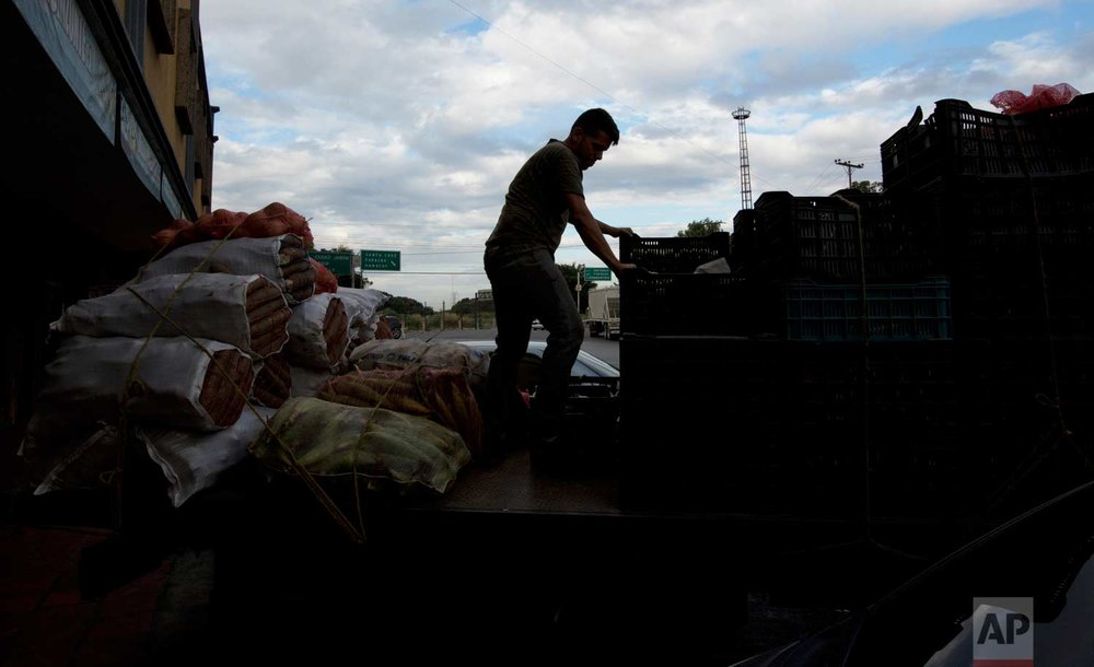 In this Jan. 22, 2018 photo, a truck driver ties down merchandise in an attempt to protect it from looters, after making a delivery to a supermarket in Villa de Cura, Venezuela. (AP Photo/Fernando Llano)  See these photos on AP Images