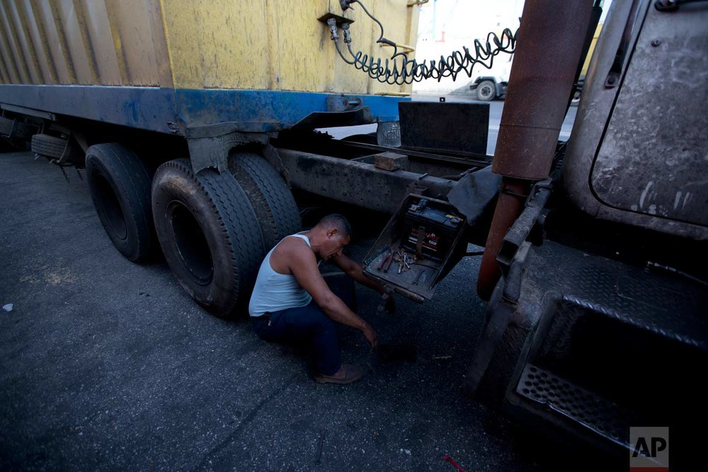 In this Jan. 23, 2018 photo, a truck driver replaces his battery after people stole his overnight while he waited to load up on corn at port in Puerto Cabello, Venezuela.(AP Photo/Fernando Llano)  See these photos on AP Images