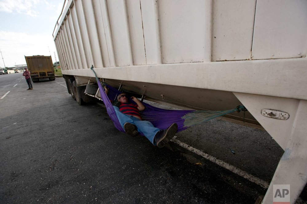 In this Jan. 23, 2018 photo, a truck driver sleeps under his truck as he wait to load up on corn at port in Puerto Cabello, Venezuela. (AP Photo/Fernando Llano)  See these photos on AP Images