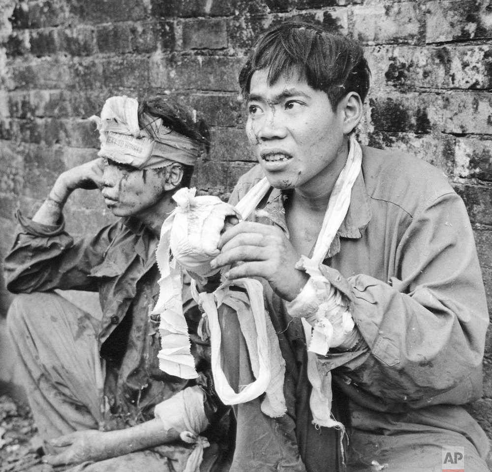 In this Feb. 27, 1968, photo, two Communist prisoners await transport to an interrogation center after South Vietnamese Rangers overran enemy positions in the Citadel of Hue, Vietnam. Early on the morning of Jan. 31, 1968, as Vietnamese celebrated the Lunar New Year, or Tet as it is known locally, Communist forces launched a wave of coordinated surprise attacks across South Vietnam. The campaign, one of the largest of the Vietnam War, led to intense fighting and heavy casualties in cities and towns across the South. (AP Photo/Dang Van Phuoc)