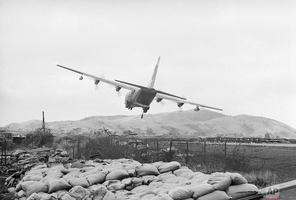 In this Feb. 23, 1968, photo, a U.S. Air Force transport plane drops supplies during a low-level pass over the U.S. Marine base at Khe Sanh, South Vietnam. In foreground is a sandbagged bunker on the base's perimeter. The planes avoid landing because of frequent Communist shelling. Early on the morning of Jan. 31, 1968, as Vietnamese celebrated the Lunar New Year, or Tet as it is known locally, Communist forces launched a wave of coordinated surprise attacks across South Vietnam. The campaign, one of the largest of the Vietnam War, led to intense fighting and heavy casualties in cities and towns across the South. (AP Photo/John Sneider)