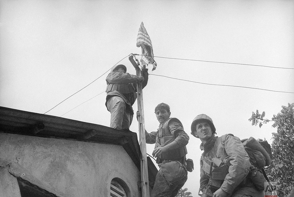 In this Feb. 22, 1968, Lance Cpl. James Avella or North Bergen, N.J., left, fastens the stars and stripes to a telephone pole near the south wall of Hue's Citadel, Vietnam. Sgt. Greg Pratt of Ojai, Calif., follows. The Marines of Alpha Company of the 1st Battalion, 5th Marine Regiment took their south wall objective after fierce fighting and heavy casualties. Early on the morning of Jan. 31, 1968, as Vietnamese celebrated the Lunar New Year, or Tet as it is known locally, Communist forces launched a wave of coordinated surprise attacks across South Vietnam. The campaign, one of the largest of the Vietnam War, led to intense fighting and heavy casualties in cities and towns across the South. (AP Photo/John Lengel)