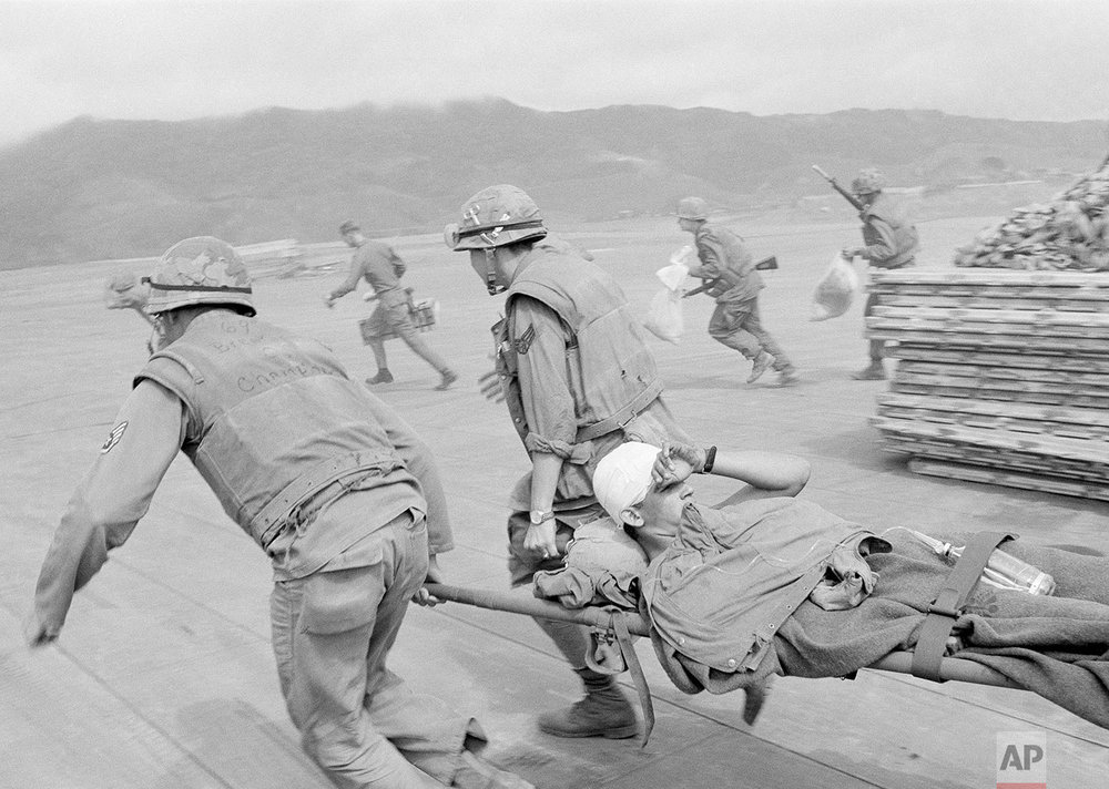 In this Feb. 11, 1968, photo, Air Force medics race across open ground past bunkers beside Khe Sanh airstrip carrying badly wounded Marines to plane while under sniper fire from guerrillas at perimeter of the area, central Vietnam. The rescue craft could stay on the ground just long enough to take on the wounded. Early on the morning of Jan. 31, 1968, as Vietnamese celebrated the Lunar New Year, or Tet as it is known locally, Communist forces launched a wave of coordinated surprise attacks across South Vietnam. The campaign, one of the largest of the Vietnam War, led to intense fighting and heavy casualties in cities and towns across the South. (AP Photo)