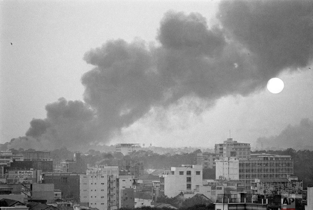 Smoke rises over battle-scarred Saigon during the Tet Offensive as the sun sets over the South Vietnamese capital on Feb. 8, 1968. Savage fighting was continuing there for the ninth consecutive day with Viet Cong guerrillas pitted against combined South Vietnamese and U.S. forces. (AP Photo/Eddie Adams)