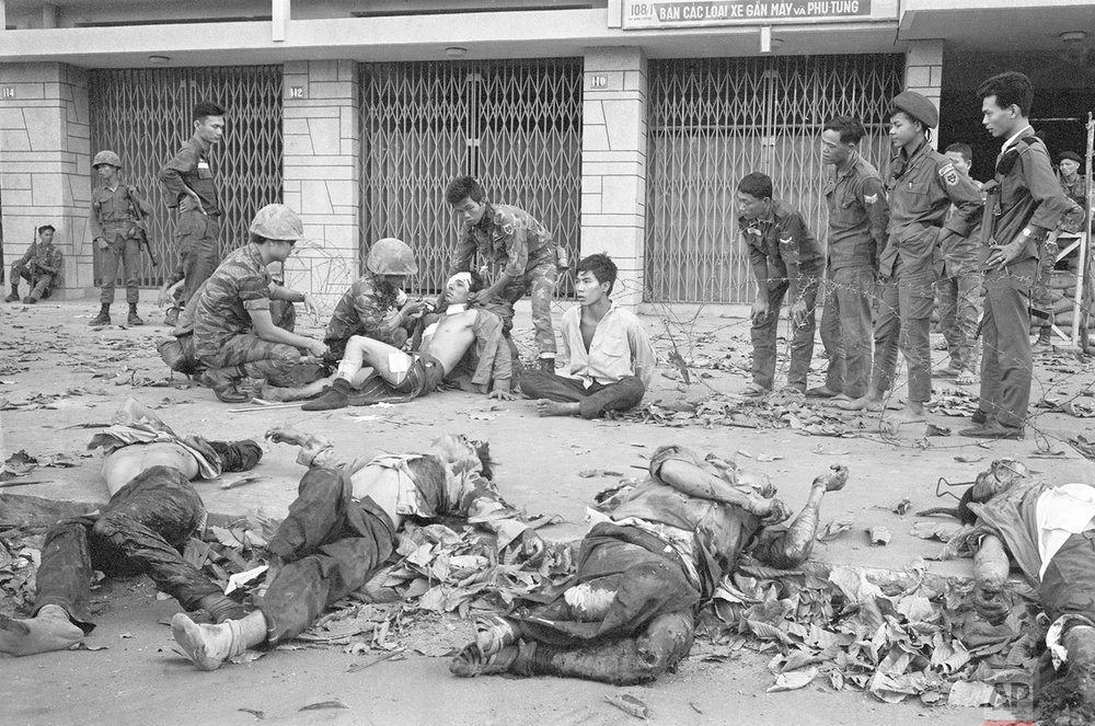 ** EDITORS NOTE: GRAPHIC CONTENT ** South Vietnamese troops tend to wounded people as bodies line a Saigon street during the Tet Offensive in early 1968. (AP Photo/Eddie Adams)