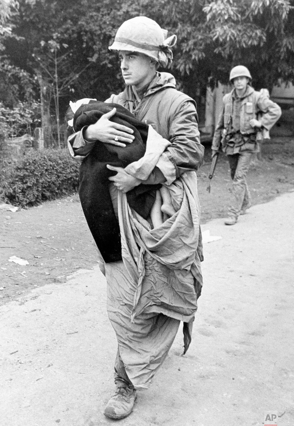 A U.S. Marine carries a blanket-wrapped wounded Vietnamese child from an aid station to an ambulance for evacuation from the Citadel in Hue, Feb. 17, 1968. The child wandered into Marine lines after he was wounded by American artillery fire directed at Red positions. (AP Photo)