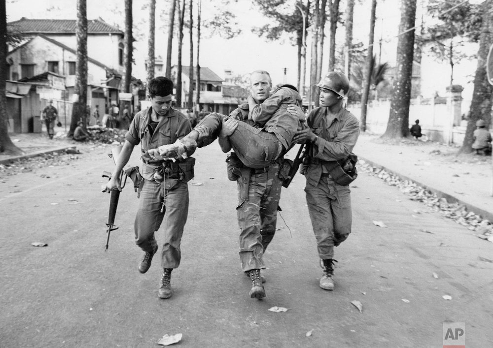 In this Feb. 6, 1968 photo, First Lt. Gary D. Jackson of Dayton, Ohio, carries a wounded South Vietnamese Ranger to an ambulance after a brief but intense battle with the Viet Cong during the Tet Offensive near the National Sports Stadium in the Cholon section of Saigon. Early on the morning of Jan. 31, 1968, as Vietnamese celebrated the Lunar New Year, or Tet as it is known locally, Communist forces launched a wave of coordinated surprise attacks across South Vietnam. The campaign, one of the largest of the Vietnam War, led to intense fighting and heavy casualties in cities and towns across the South. (AP Photo/Dang Van Phuoc)
