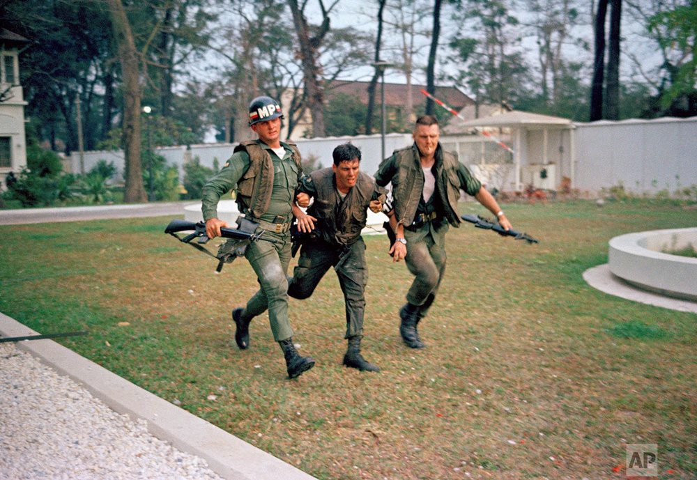 In this Jan. 31, 1968 photo, two U.S. military policemen aid a wounded fellow MP during fighting in the U.S. Embassy compound in Saigon, Vietnam, at the beginning of the Tet Offensive. (AP Photo)