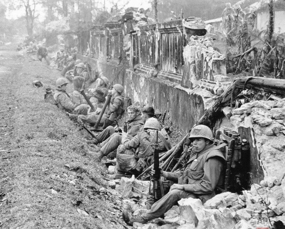 In this Feb. 1968 photo, a unit of the 1st Battalion, 5th Regiment U.S. Marines, rests alongside a battered wall of Hue's imperial palace after a battle for the Citadel during the Tet Offensive. The Marines reported heavy casualties in street fighting in the ancient capital city of Vietnam. Early on the morning of Jan. 31, 1968, as Vietnamese celebrated the Lunar New Year, or Tet as it is known locally, Communist forces launched a wave of coordinated surprise attacks across South Vietnam. The campaign, one of the largest of the Vietnam War, led to intense fighting and heavy casualties in cities and towns across the South. (AP Photo)
