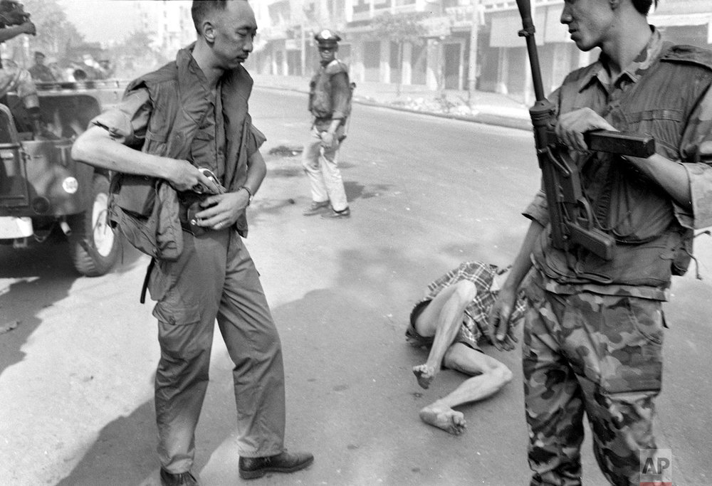 ** EDS NOTE: GRAPHIC CONTENT ** South Vietnamese Gen. Nguyen Ngoc Loan, chief of the national police, holsters his gun after executing suspected Viet Cong officer Nguyen Van Lem (also known as Bay Lop) whose body lies on a Saigon street Feb. 1, 1968, early in the Tet Offensive. (AP Photo/Eddie Adams)