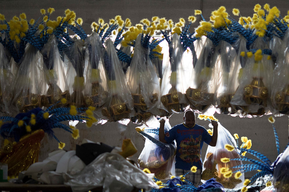 In this Jan. 16, 2018 photo, a worker carries costume accessories for the upcoming Carnival, inside the Paraiso do Tuiuti samba school in Rio de Janeiro, Brazil. (AP Photo/Leo Correa)