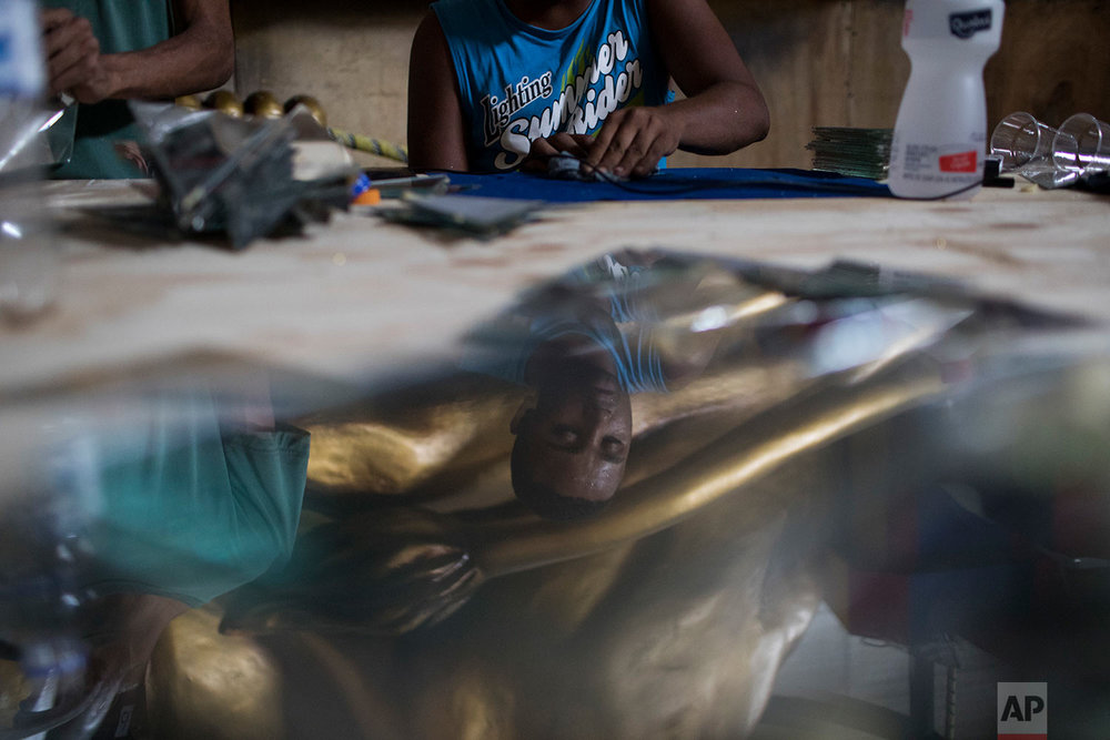 "In this Jan. 16, 2018 photo, a man cleans glass that will be part of a carnival float used by the the Paraiso do Tuiuti samba school, whose theme this carnival is Brazil's history with slavery, in Rio de Janeiro, Brazil. ""Our music questions whether slavery is actually over,"" said Jack Vasconcelos, the group's art director. (AP Photo/Leo Correa)"