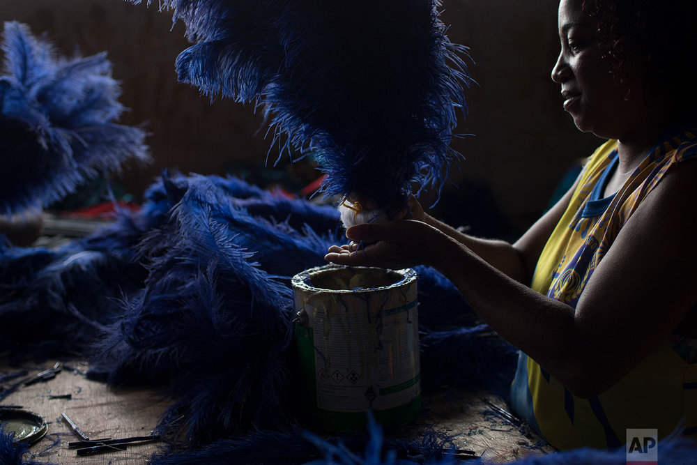 In this Jan. 16, 2018 photo, a woman creates costumes for the Paraiso do Tuiuti samba school's upcoming Carnival performances, which will address the subject of slavery in Brazil, in Rio de Janeiro, Brazil. Brazil was the last country in the Americas to abolish slavery, and 130 years later the impact is still very much felt in this content-size nation. (AP Photo/Leo Correa)