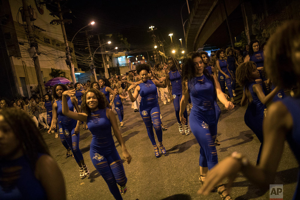 In this Jan. 22, 2018 photo, members of the Paraiso do Tuiuti samba school rehears their dances and songs, which make reference to Brazil's history with slavery, in the streets of Rio de Janeiro, Brazil. The samba school notes that Brazil is one of the world's most unequal countries in terms of income distribution, and that its top politicians and businessmen are predominantly white while more than 50 percent of citizens identify as black or mixed race. (AP Photo/Leo Correa)