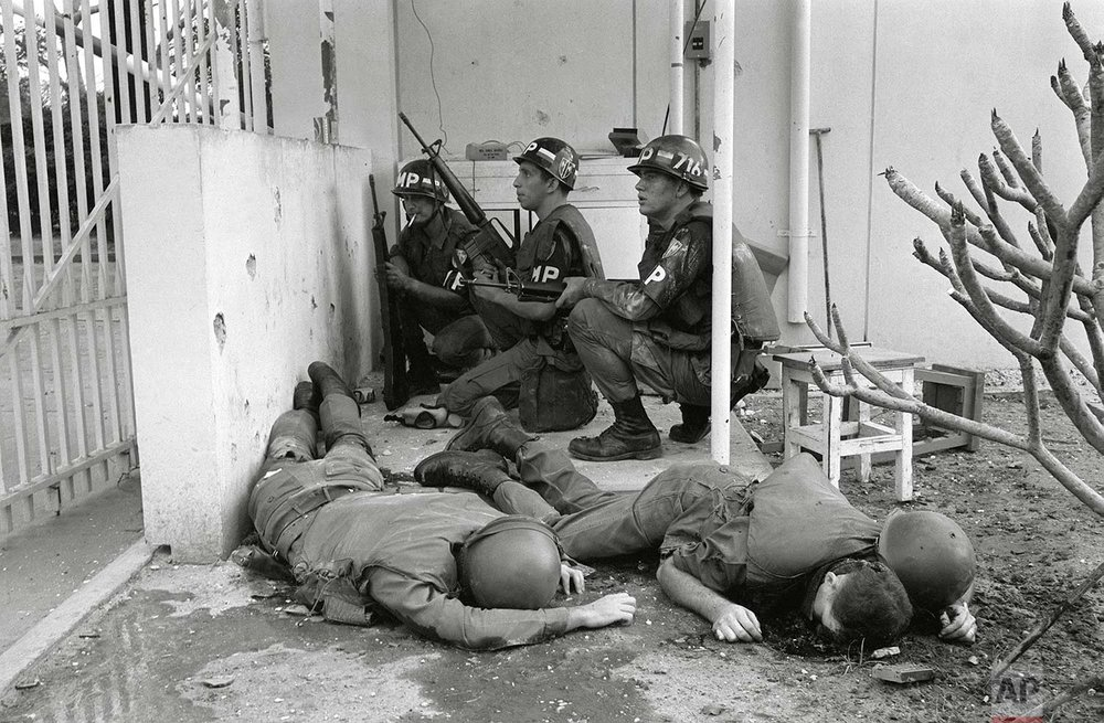 ** EDS NOTE: GRAPHIC CONTENT **  With dead U.S. soldiers in the foreground, U.S. military police take cover behind a wall at the entrance to the U.S. Consulate in Saigon on the first day of the Tet Offensive, Jan. 31, 1968. Viet Cong guerrillas had invaded the grounds of the U.S. Embassy compound in the earliest hours of the coordinated Communist offensive. (AP Photo/Hong Seong-Chan)