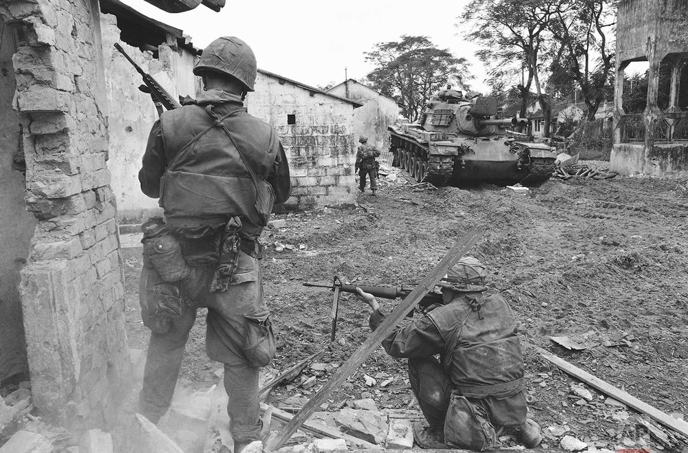 A soldier, upper left, climbs from balcony to balcony while another, helmeted in center foreground, fires into a room during an effort to flush out Viet Cong fighters in a still-under construction hotel in Saigon, Vietnam, Jan. 31, 1968, near the South Vietnamese presidential palace. South Vietnamese and U.S. forces combined to halt an attack on the capital by the Cong guerrilla forces. (AP Photo)