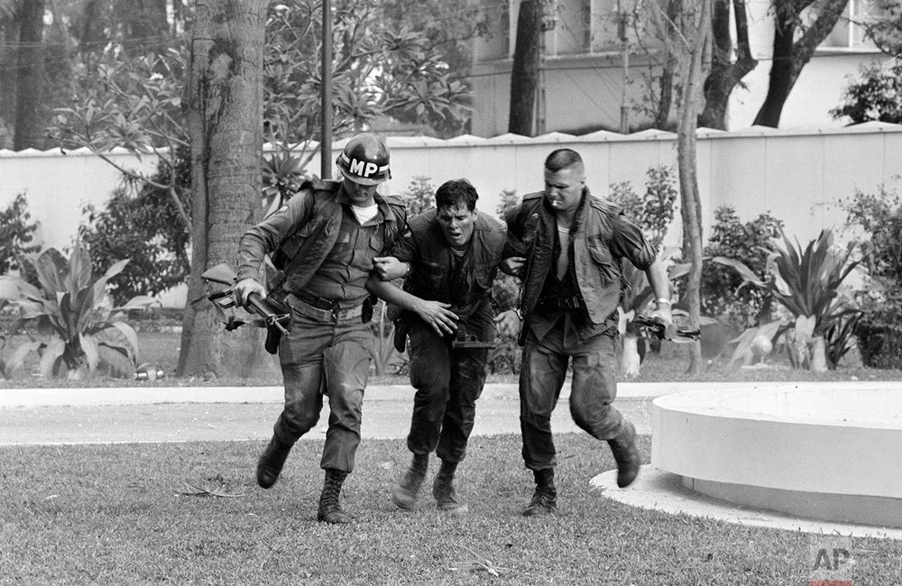 Two U.S. military policemen aid a wounded fellow MP during fighting in the U.S. Embassy compound in Saigon, Jan. 31, 1968, at the beginning of the Tet Offensive. A Viet Cong suicide squad seized control of part of the compound and held it for about six hours before they were killed or captured. (AP Photo/Hong Seong-Chan)