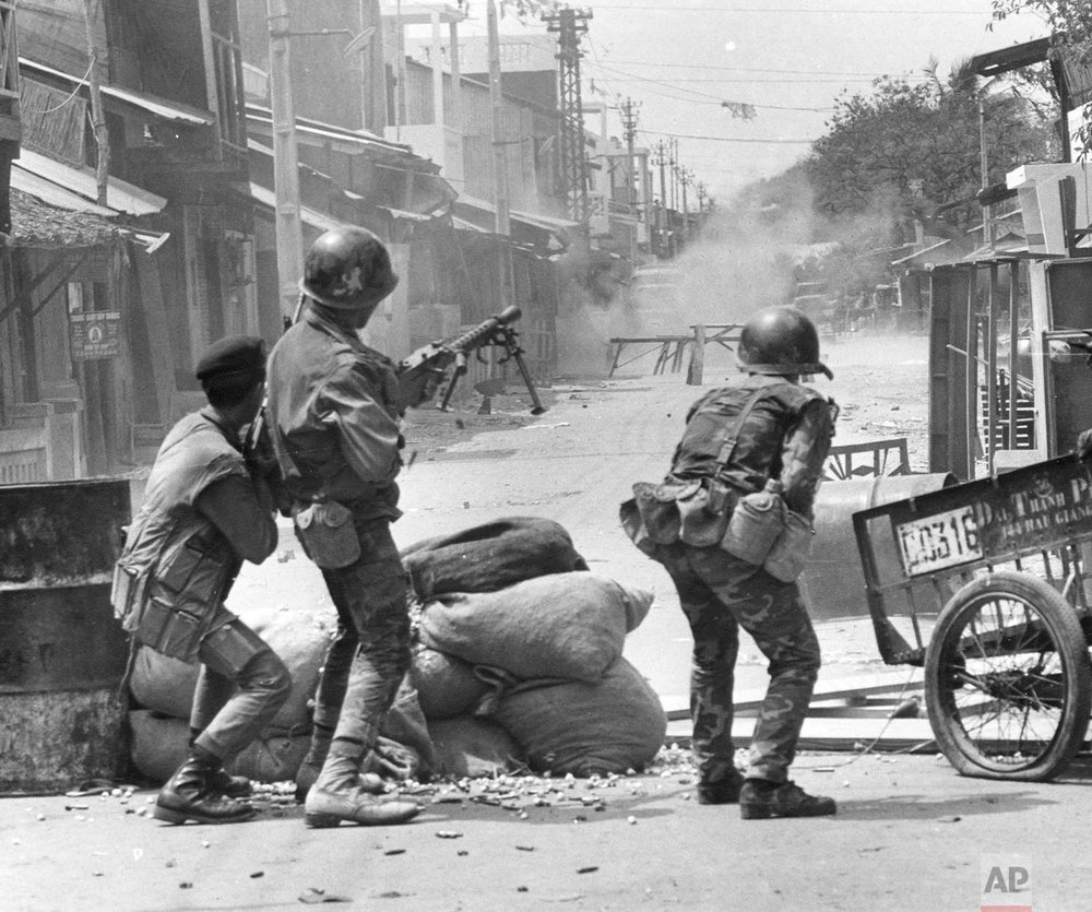 South Vietnamese Rangers and police fire automatic weapons at trucks and people in the streets of Cholon, the Chinese sector of Saigon, during the Tet Offensive, Feb. 7, 1968. The street barricades had been set up by Viet Cong guerrillas. (AP Photo/Dang Van Phuoc)
