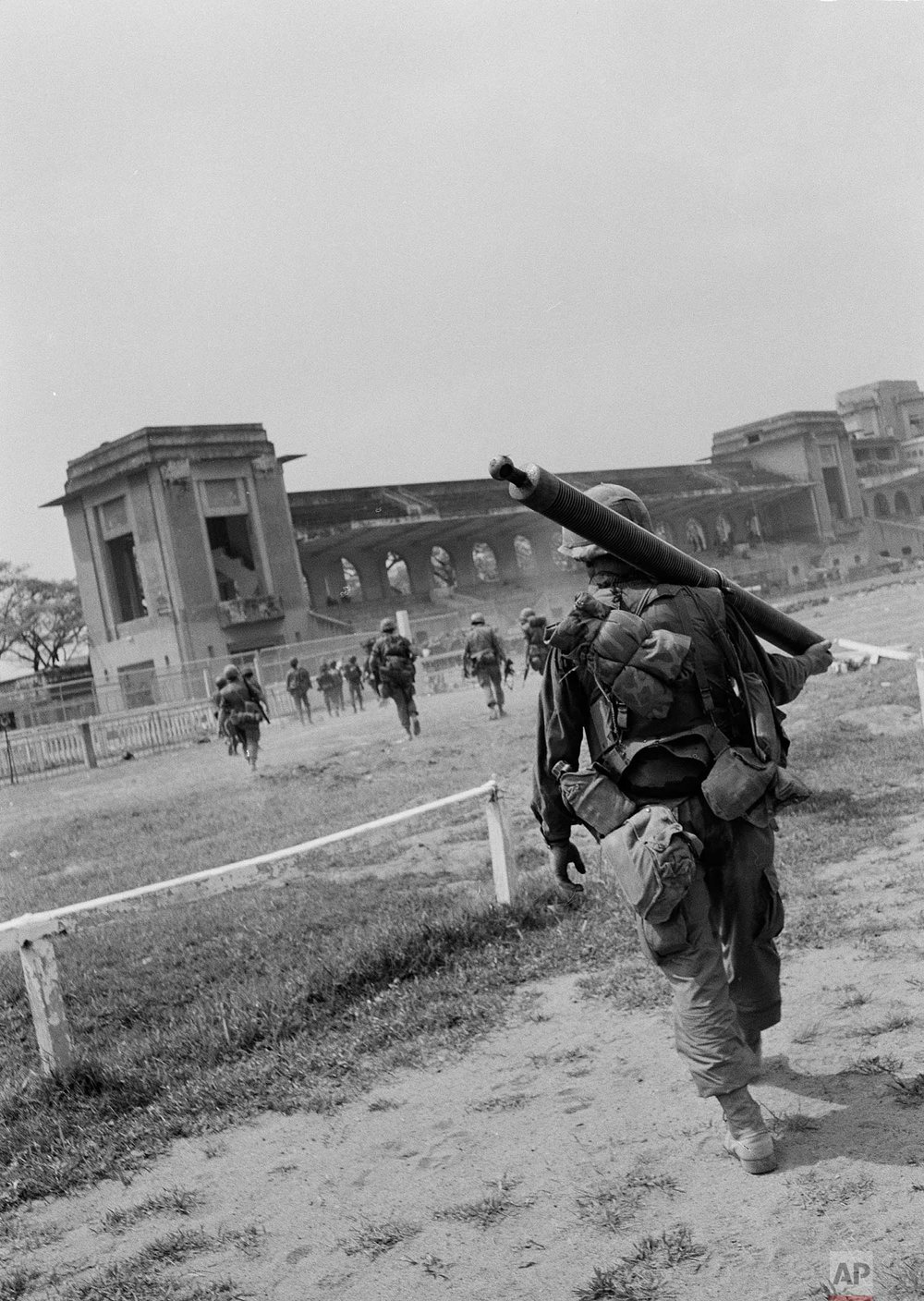 U.S. troops of the 199th Light Infantry Brigade march toward the grandstand after they were lifted to the Phu Tho racetrack in Saigon, South Vietnam, during the Tet Offensive, Feb. 9, 1968. They are there to help South Vietnamese force in routing the Viet Cong out of Saigon's Chinese district. The trooper in the foreground carries a mortar tube. (AP Photo)
