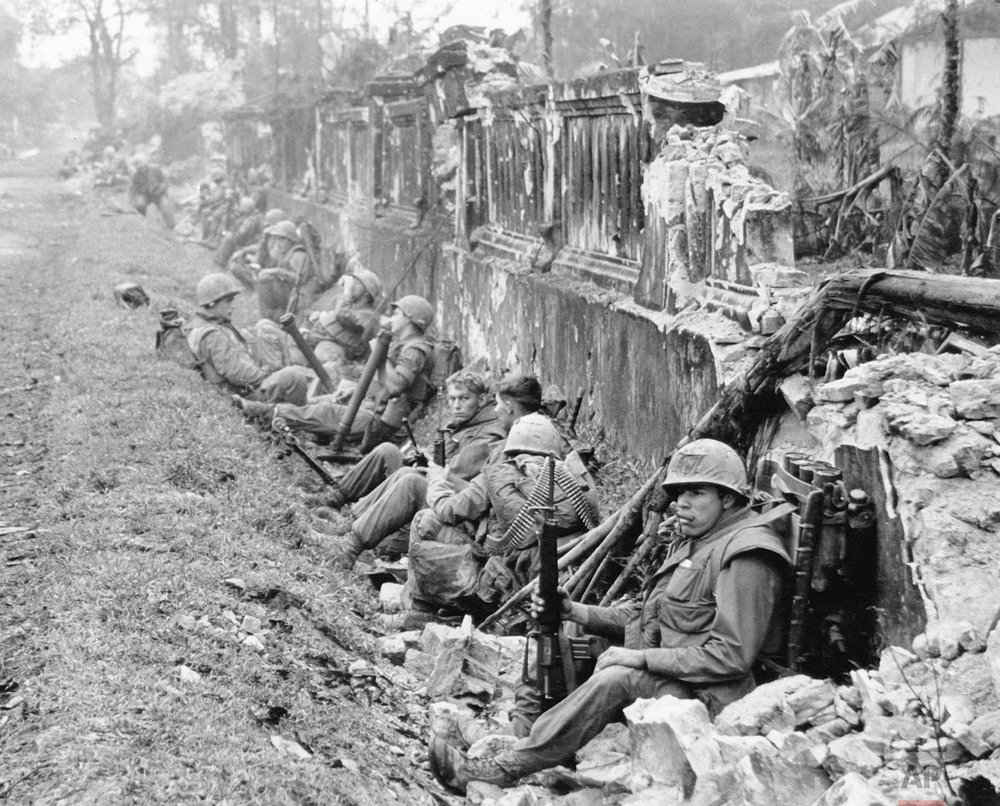 A unit of the 1st Battalion, 5th Regiment U.S. Marines, rests alongside a battered wall of Hue's imperial palace after a battle for the Citadel in February 1968, during the Tet Offensive. The Marines reported heavy casualties in street fighting in the ancient capital city of Vietnam. (AP Photo)