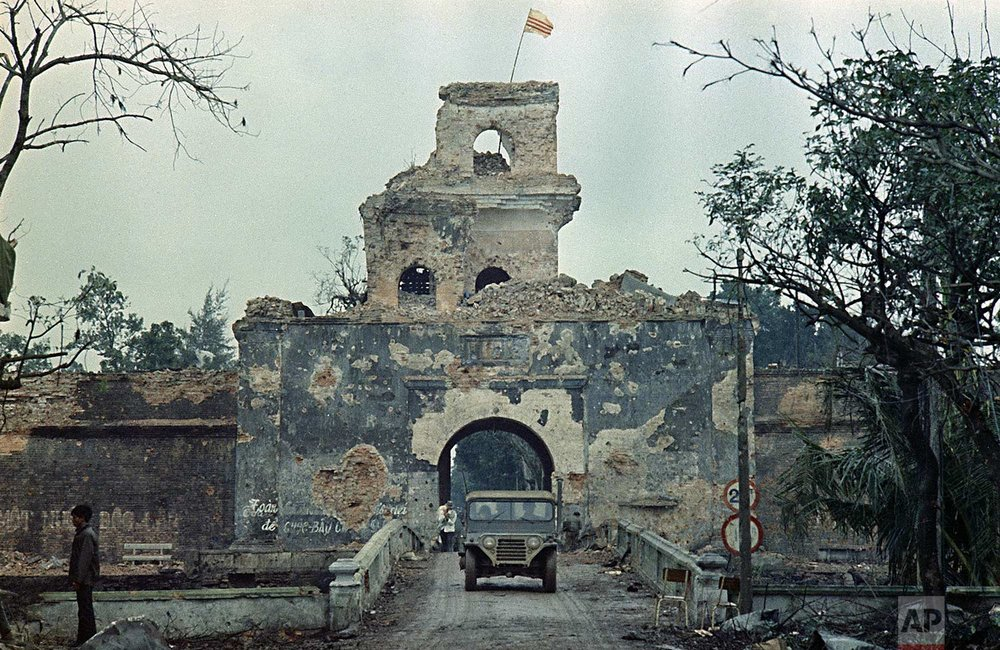 The Vietnam flag flies atop a tower of the main fortified structure in the old citadel as a jeep crosses a bridge over a moat in Hue, during the Tet Offensive, Feb. 1968.  (AP Photo)