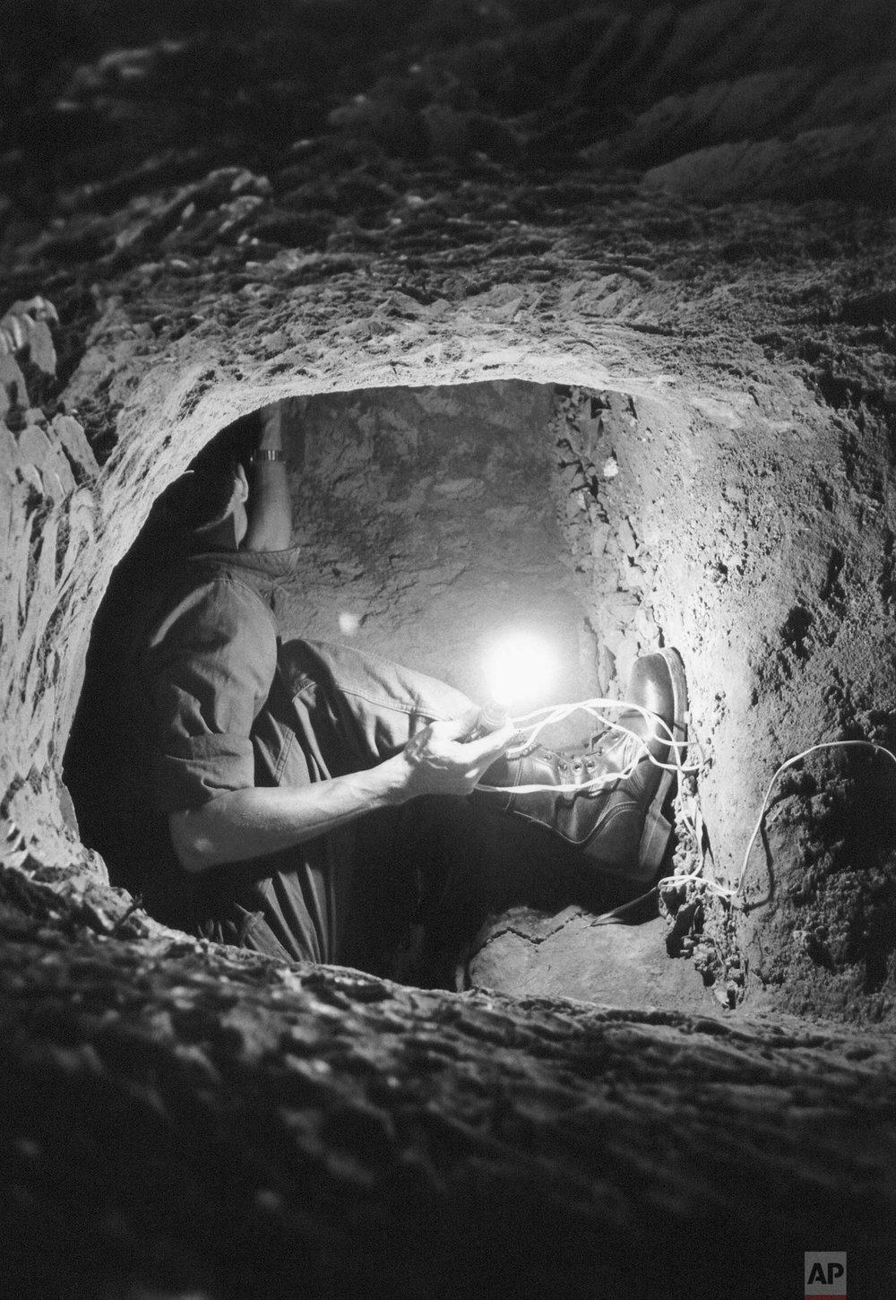 A Vietnamese national policeman holds a lightbulb as he crawls through a tunnel and bunker network leading from pagoda grounds to an outside entrance in the Gia Dinh province on the outskirts of Saigon, March 3, 1968. It is thought that the system was used by the Viet Cong to infiltrate men into the area in the Tet Offensive. The bunker itself is capable of holding up to twelve persons. (AP Photo/Le Ngoc Cung)