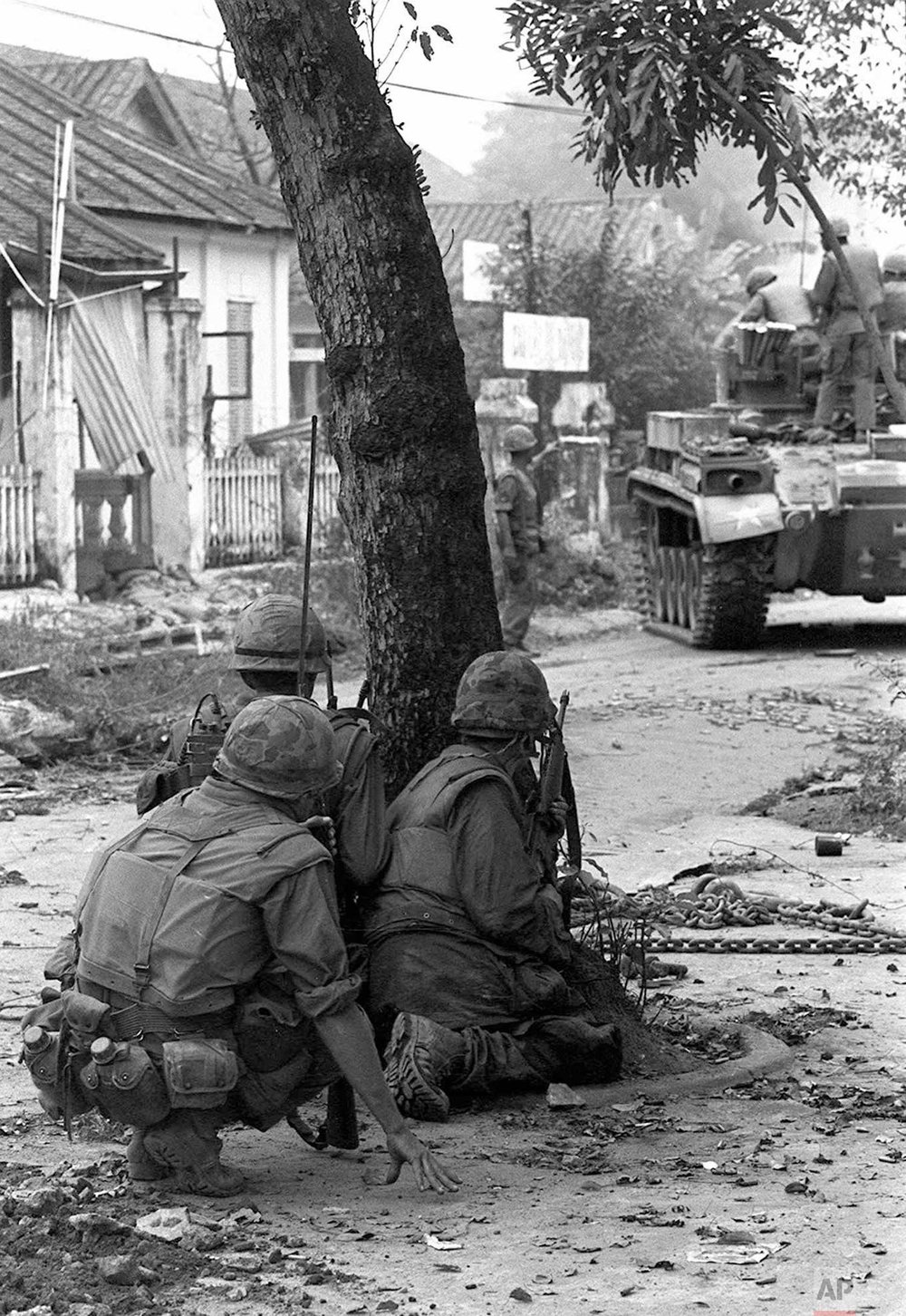 U.S. Marines, supplemented by a tank, take cover behind a tree near the southern bridgehead on the Perfume River, in Hue, Vietnam, Feb. 4, 1968 as they fight well-armed North Vietnamese troops for the fifth straight day. The communists continued to hold on to the major portion of the city. (AP Photo)