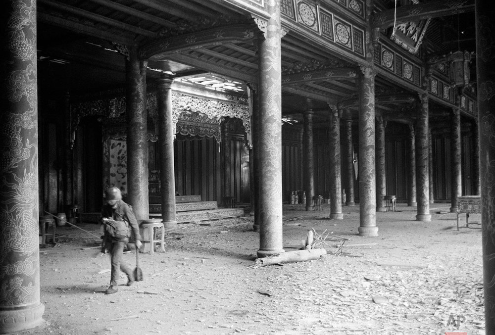 A soldier walks among dirt and debris of battle at the ornate Imperial Palace in the Citadel of Hue during the Tet Offensive, February 1968. (AP Photo/Eddie Adams)
